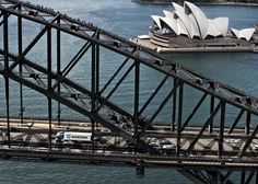 A Maersk container crossing the Sydney Harbour Bridge with the Opera House in the background.