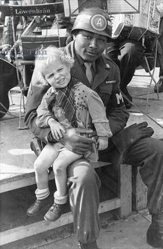 American soldier with a German child on his knee, Munich, 1945.
