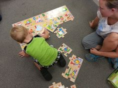 Thor fits the alphabet pieces together - with a little coaching from Mom.