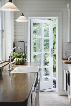love the paneling, brightness, glass side door & colour of countertops (wood?)