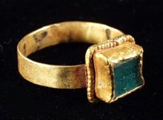 GERMANIC GOLD AND GLASS RING           VI c. A.D.   Hammered thick sheet gold hoop with the ends soldered to a square backing plate of a high box-type bezel, set with flat emerald-colored glass. Bezel's perimeter decorated with beaded wire. L. 22 mm, 18 x 16 inside.