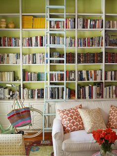 """Benjamin Moore's Tasty Apple brightens up the bookcase in the library. """"I change the pillows out a couple of times are year, and it literally creates the effect of a new room,"""" says Lily Kanter of Serena & Lily."""