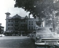 Photo taken in summer of 1957 looking east along a row of cars parked next to Central Park. In the background is the S.N. Ford Building, housing, at that time, Hotpoint appliances, Consolidated Insurance, Shrigley's Shoes and a number of apartments. To the left, the edge of S.N. Ford's grand downtown home--to the right of the Ford Flats, the International Order of Odd Fellows Hall.