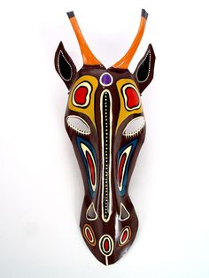 """Antelope Mask Wall Hanging. African masks should be seen as part of a ceremonial costume, and animals are common subjects in African masks. Animal masks connect people with the spirit world that traditional African beliefs say inhabit the forests and open savannas. An animal is also a symbol of specific virtues. In African mythology, the antelope symbolizes vivacity, velocity, beauty and visual sharpness.    Height: 17""""  Width: 7.5""""  Artist: Mkankha Brothers  Made In: Zimbabwe  $58.00"""