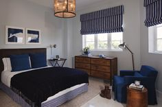 Decorpad - Lauren Stern Design    Big boy's blue bedroom deisgn with charcoal gray headboard, baby blue walls paint color, blue recliner, round wood accent table, white & blue striped roman shades, blue pillows, navy blue, throw, white & blue striped bed skirt and walnut dresser.