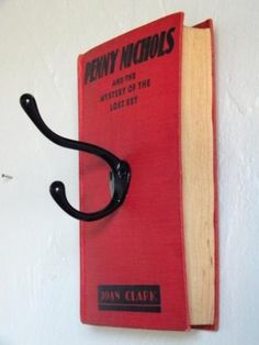 What a good idea - instead of a coat hook maybe use more than one to create a new way to hand anchor charts or some other use... just love using old books to upcycle into useful decoration /// blog where the picture is found has pictures only