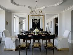 Be still my heart!  source: Candace Cavanaugh Interiors  Stunning dining room with quatrefoil molding on ceiling! Beautiful pale gray wood flooring. White slipcovered captain chairs with gold banding. French black side chairs with leopard print seat cushions and oval dining table. Gold floor length mirror with and pale gray paint with crisp white molding.