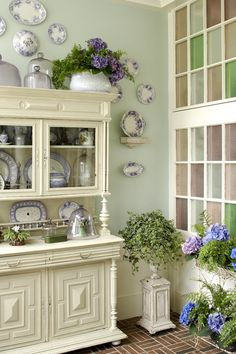 love the gorgeous hutch, the play of the blue and white china against the soft green wall, the flowers, and the simple stained glass windows too