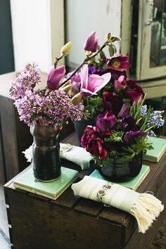 Lilac, magnolia blossom, hellebores, muscari, and anenome in California pottery, on Malibu tile, with hand-embroidered napkins and vintage ribbon