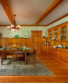 Newly built Craftsman Style Home. Typical of Craftsman-era dining rooms, a high wainscot with battens, brackets, and a plate rail accompanies a beamed ceiling and a built-in sideboard.