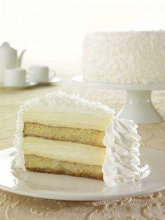 Piña Colada Cake Cheesecake: A seasonal favorite - moist white cake layered with Original Cheesecake, pineapple, coconut and rum.