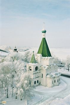 Green steepled church in snow