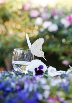 Butterfly name tags on wine glasses.