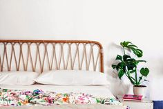 A bright white bedroom pops thanks to a colorful, floral bedspread and houseplant.