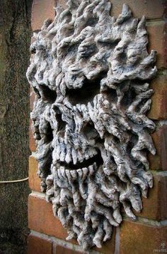 This was done out of expanding foam, build up to desire size and carve out eyes, teeth and nose with a knife. Paint. Weather proof too. - Can do similar craft out of paper mache embedded with seeds and placed on ground. Might be better as a mass of various skeletons of various species.