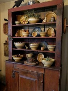 Wonderful old American cupboard filled with antique pottery and stoneware pieces.
