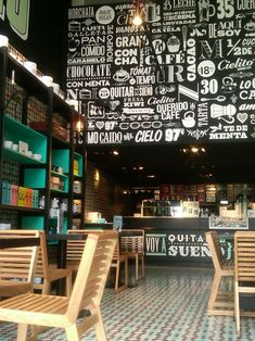 I love the different words all over the wall above the tills and the pops of turquoise in the bookshelf. I also like the horizontal panels on the backs of the chairs, they let the light pass through them and help open the space.