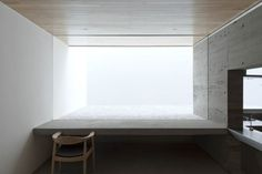 Frameless window looking out onto a white patio. House-T by Tsukano Architect Office