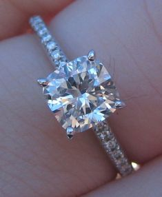 cushion cut diamond set in a white gold fishtail pave setting.