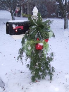 A little snow is the perfect finish to a Bright Lime Green Bow, Large Red Ornaments. and lots of Greenery - Christmas Mailbox