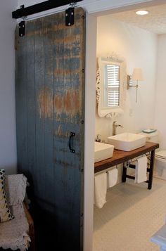 Use an old farm door as to enter a master bath + using a farm supplier for the hardware saved 75% over retail