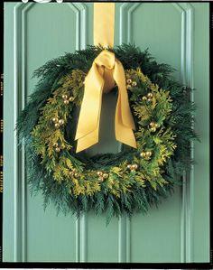 Tiny golden bells, cedar and a satin bow make for a timeless front door wreath.