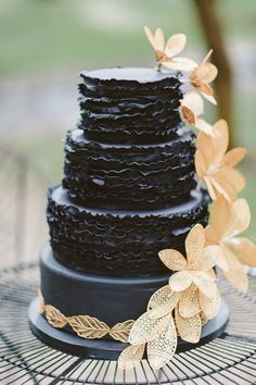 Ruffled Black wedding cake with rustic flower accents.