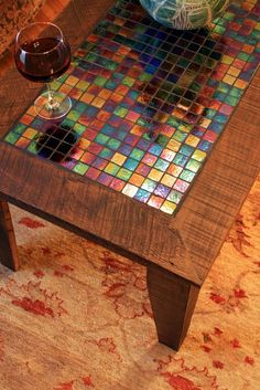 """Iridescent glass tile inlay in coffee table."" Or if you're looking to protect the top of you coffee table, you could get a cheap plastic place mat or some shelf liner and hot glue a mosaic with tiles bought at Michaels. That way it's removable and protective."