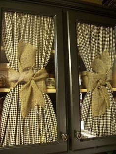 gingham checked curtains tied with burlap for a window / cabinet door with glass  This is a great option for a seasonal change, Spring or Holidays. Kitchens are so permanent, it is hard to give an affordable makeover; this is brilliant!