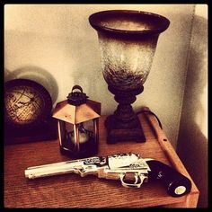 The gun is an avon bottle and the globe is a bookend. Everything in this picture was found at different thrift shops! $4 for both bookends, $2 for the lantern, $1.50 for the bottle, and $12 for the lamp.