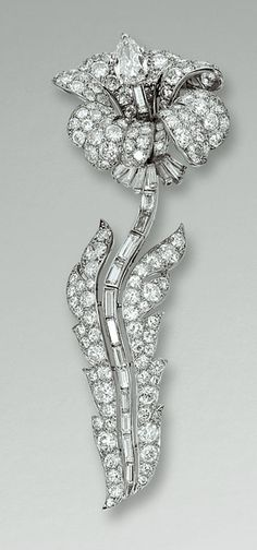 DIAMOND BROOCH, CARTIER Designed as a lily,  the flower head set with circular-cut diamonds, to a pear-shaped stone pistil, the articulated stem set with calibré-cut diamonds, between diamond set leaves, mounted in platinum, signed Cartier Paris and numbered, French assay and maker's marks.