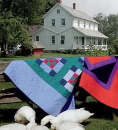 Amish quilts air out on a fence.