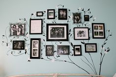 Wall decor inspiration...combine a reusable tree wall decal with a collection of photo frames.