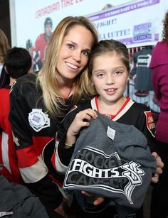 Erin Phillips, wife of Chris Phillips, and their daunter Zoe sell #HockeyFightsCancer t-shirts prior to the Ottawa Senators game.
