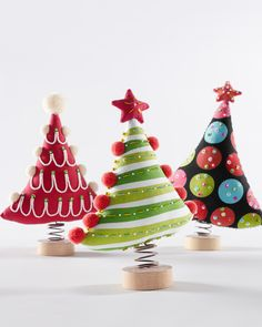 Embellished with pom-poms, beads, sequins and funny toppers, our trio of trees in bright cotton canvas have springs for trunks, making each design wobble and bobble for added fun