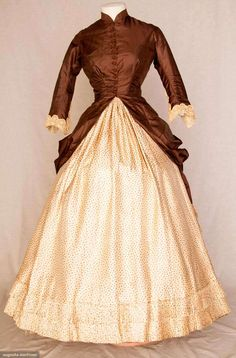 """TWO TONE SILK BUSTLE DRESS, c. 1880 Go Back Lot: 203 November 10, 2010 - St. Pauls - NYC New York, NY Chocolate brown polonaise bodice extends to side draped & back bustle over-skirt, 10 crochet ball buttons, cream silk twill skirt w/ tiny brown flower head print, skirt has CB square insert of solid brown & bustle ties, embroidered lace cuffs, tan cotton lining, B 32"""", W 23"""", Skirt L 37"""", ..."""