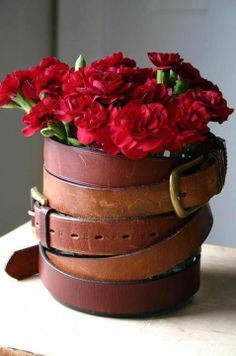 Have an old belt in the closet that doesn't fit well any longer? Repurpose an old belt by wrapping it around a coffee can and then fill it with cut flowers for an interesting centerpiece. ~Budget101 belt