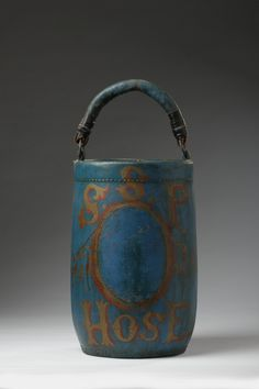 """AMERICAN PAINTED AND GILT-DECORATED LEATHER FIRE BUCKET - In blue paint, gilt and edged in red paint with a vacant medallion beneath the letters """"S.S.P"""" and above """"HOSE."""" Height 12 ½ inches."""