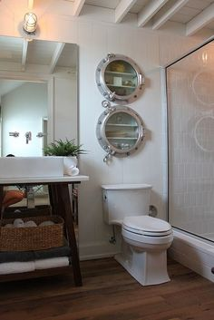 Uses for ships portholes I just bought: Porthole medicine cabinets add a nautical element to this bath