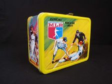 """Baseball Lunch Box: This yellow metal lunch box was made by Thermos in 1968. It has a hinged lid and a single silver snap. The box features colorful scenes of baseball players in action on the lid and sides of the lunch box. The back has a magnetic playing field, and a scoreboard and playing instructions are located on the bottom. The inside has two """"Spin the Arrow"""" baseball game packets, each with four magnetic markers to use as runners in the game."""