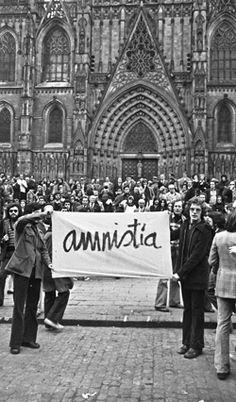 """Imatge dels manifestants de l'1 de febrer de 1976 davant la catedral de Barcelona desplegant un  llençol amb la paraula """"amnistia"""". © Pepe Encinas."""