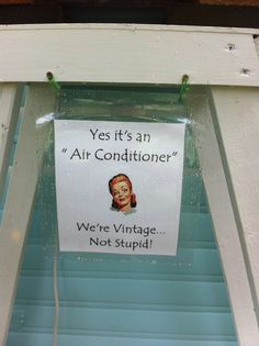 Sign hanging under ladder as a prop for window air conditioner in a vintage camper window.