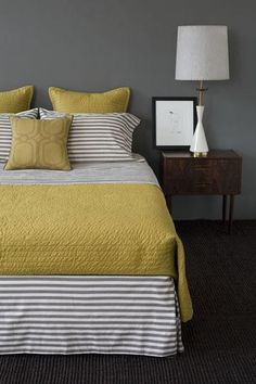 Yellow and grey bedroom with mid-century modern nightstand and lamp