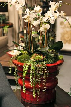 Arrange potted plants (doubling as favors) in one larger pot, use sheet moss to cover.  Would be fun to use a mix of orchids, succulents, etc