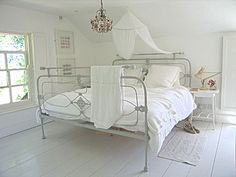 Beautiful iron bed frame adds visual interest to all white bedroom
