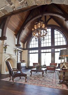 An amazing living room space gets a Gothic touch from a ribbed, vaulted ceiling and a stone archway. Light colored walls and a full-wall arched window add light and contrast.  (viaHendel Homes, Rick & Amy Hendel)