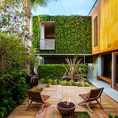 "The patio feels like an extension of the family room thanks to a series of pivoting doors. To create a sense of lush enclosure and block views of a parking lot next door, the fence is lined with tall plants such as angel's trumpet and princess flower. The walls and rooftop were covered with waterproof vinyl and modular cells that contain rooted succulents, grasses, yarrow, lantana, and ice plant to greatly expand the ""garden"" space."