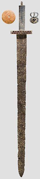 Espada de guarda en placa de tipo nómada (Sármato-Alano o Huno). Hermann Historica. Subasta 51 Lot Nr. 2147, A ceremonial sword with silver hilt. Eastern Europe, early Migration Period, between 375 and 450 A.D. Empuñadura y guarda de plata que en la parte delantera lleva un aplique de oro con decoración cloissoné (tabicada) de granates. La dragona de la espada estaba provista de un amuleto o talismán, colgante, de ámbar.