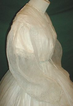 """Gossamer 1860's two piece gauze dress, de-accessioned from NY city museum. Fabric has scattered tiny aqua blue dot pattern. Bodice line with cotton camisole that has short lace trimmed sleeves & front hook & eye closure. Neck, shoulders, armscyes are piped. Skirt unlined. Bust: 30""""; Waist: 22""""; skirt length: 43""""; width at hem: 174""""."""