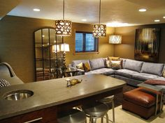Love the light fixtures, concrete countertops and grey sofa